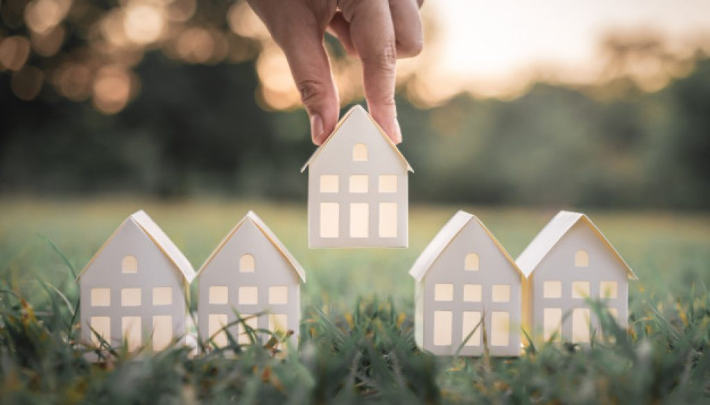 hand-choosing-white-paper-house-model-from-group-house-green-grass_42691-545