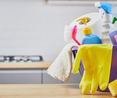 Cleaning set: sponge, bottle , glove, brush, spray on table and gray kitchen background
